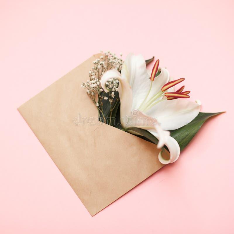 L'appartement décoratif étendent la composition avec l'enveloppe et les fleurs de papier d'emballage Configuration plate, vue sup images stock