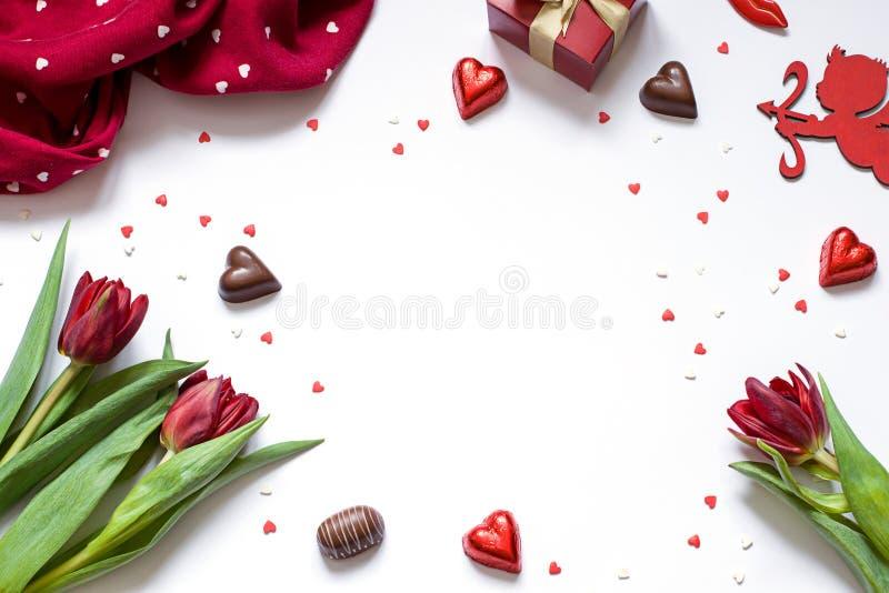 L'appartement de cadre de Saint-Valentin s'étendent sur le fond blanc avec le cupidon, le chocolat et les fleurs photos libres de droits