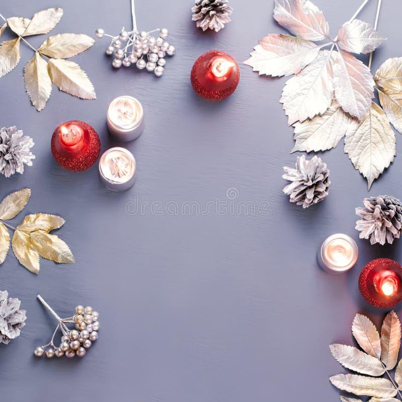 L'appartement de concept d'hiver s'étendent avec les feuilles argentées, la lanterne, les bougies et le café chaud Fond de cadre  images stock