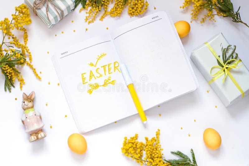 L'appartement de ressort de Pâques s'étendent avec des fleurs de mimosa, un bloc-notes photos stock