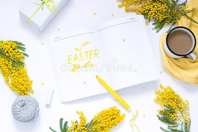 L'appartement de ressort de Pâques s'étendent avec des fleurs de mimosa, un bloc-notes et un lapin photo stock