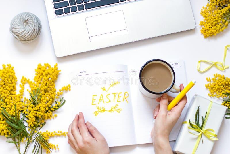 L'appartement de ressort de Pâques s'étendent avec les fleurs jaunes, l'ordinateur portable et une tasse de café La main de la fe images stock