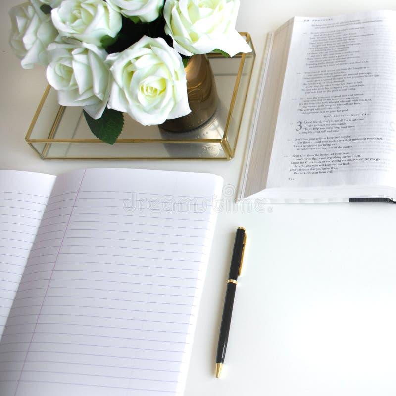 L'appartement s'étendent avec différents accessoires ; bouquet de fleur, roses blanches, livre ouvert, bible photographie stock