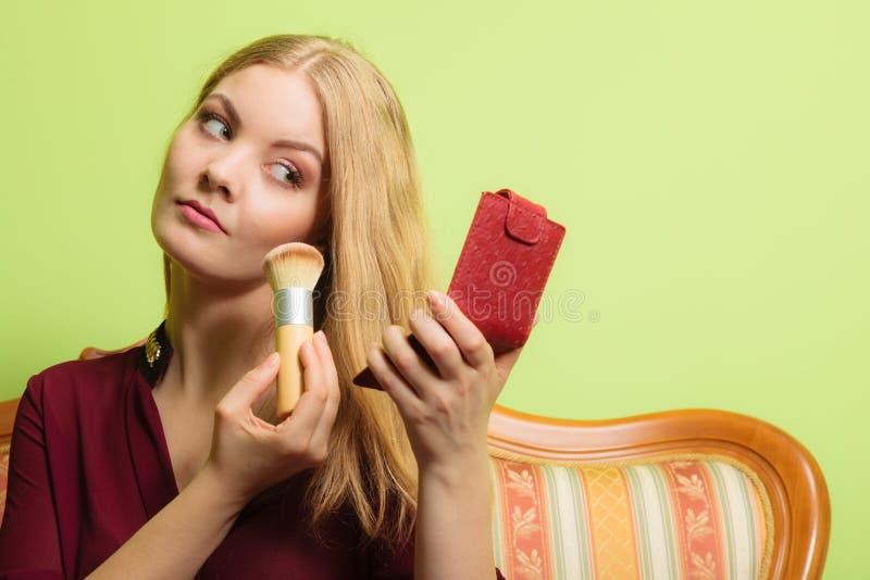 L'application attrayante de femme composent avec la brosse photo stock