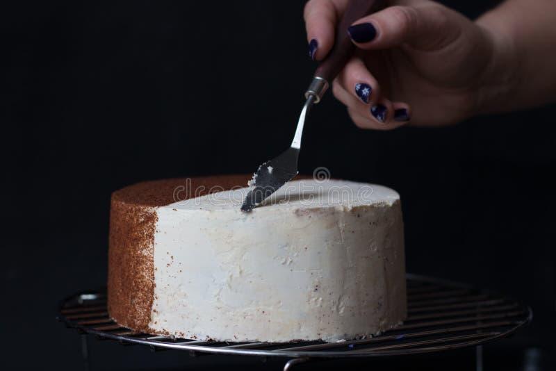 L'application de la crème sur le gâteau est blanche sur un fond noir images libres de droits