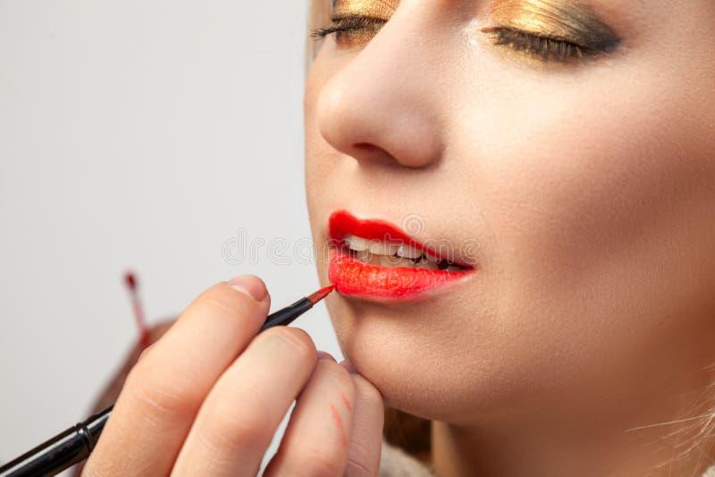 L'application en gros plan sur les lèvres, l'artiste de maquillage tient une brosse dans sa main et applique le rouge à lèvres ro photos stock