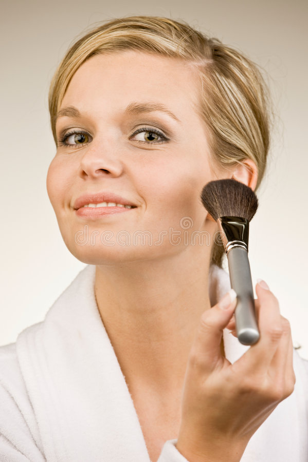 L'applicazione affascinante della donna arrossisce con la spazzola di trucco immagini stock libere da diritti