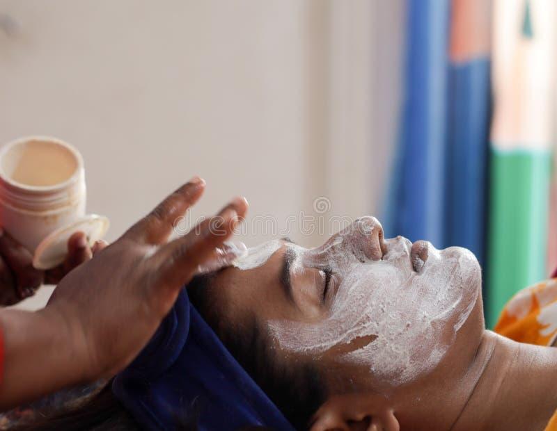 L'applicazione della crema facciale della maschera del pacchetto sul fronte di una signora con la banda dei capelli con gli occhi immagini stock libere da diritti