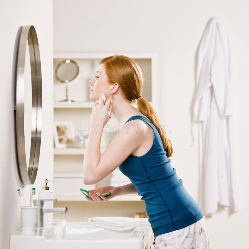 L'applicazione della donna arrossisce con la spazzola di trucco fotografia stock