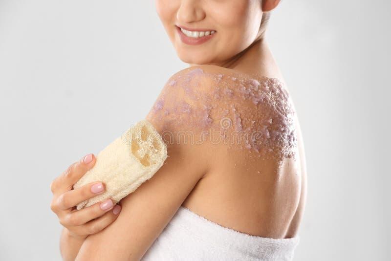 L'applicazione della donna naturale sfrega sul suo corpo contro fondo leggero fotografie stock libere da diritti