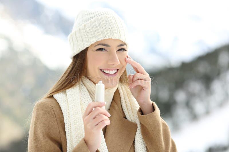 L'applicazione felice della donna idrata la crema in fronte immagine stock libera da diritti