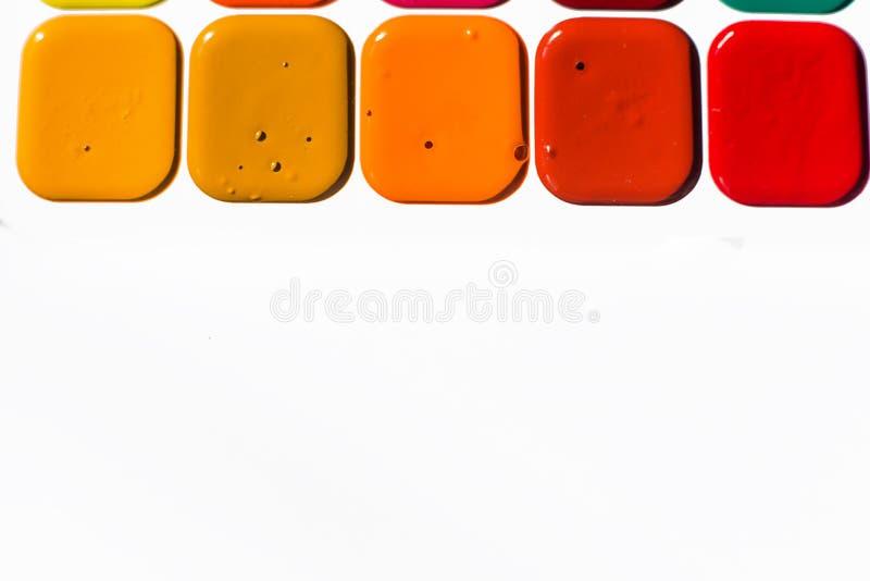 L'aquarelle lumineuse multicolore peint des nuances chaudes étroitement  Un cadre des peintures sur un fond blanc photographie stock libre de droits
