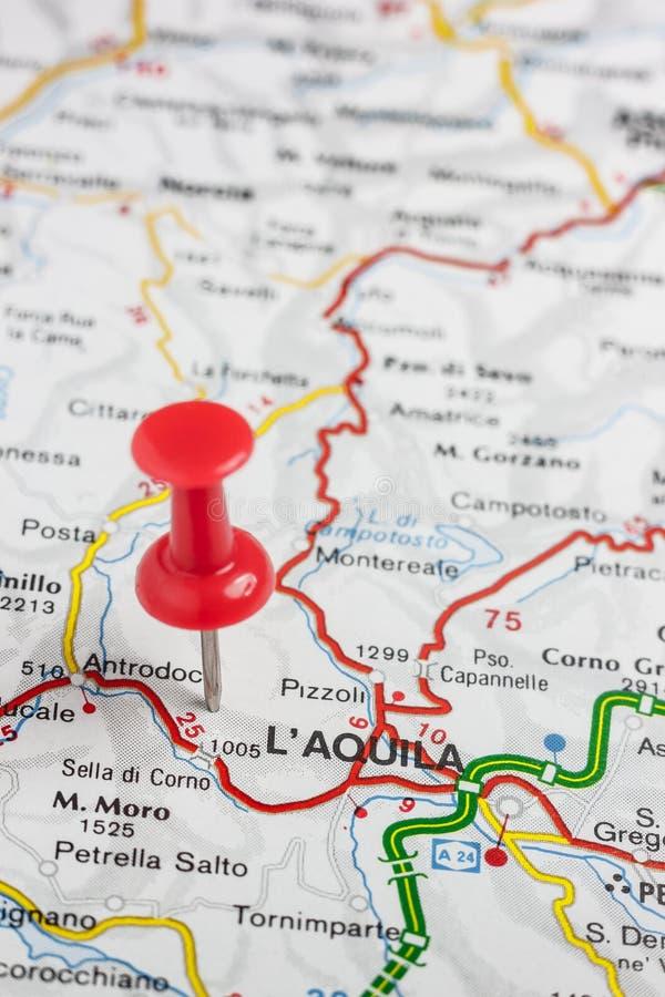 L& x27; Aquila steckte auf eine Karte von Italien fest stockbild