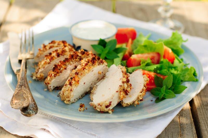 L'arachide coupée en tranches a couvert le blanc de poulet d'une croûte avec de la salade fraîche image libre de droits