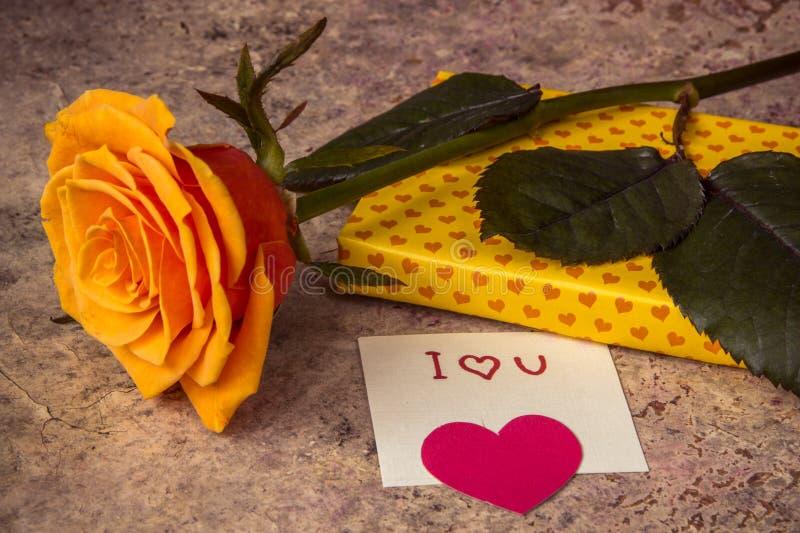 L'arancia è aumentato, regalo coperto in carta hearted e nota ti amo fotografie stock