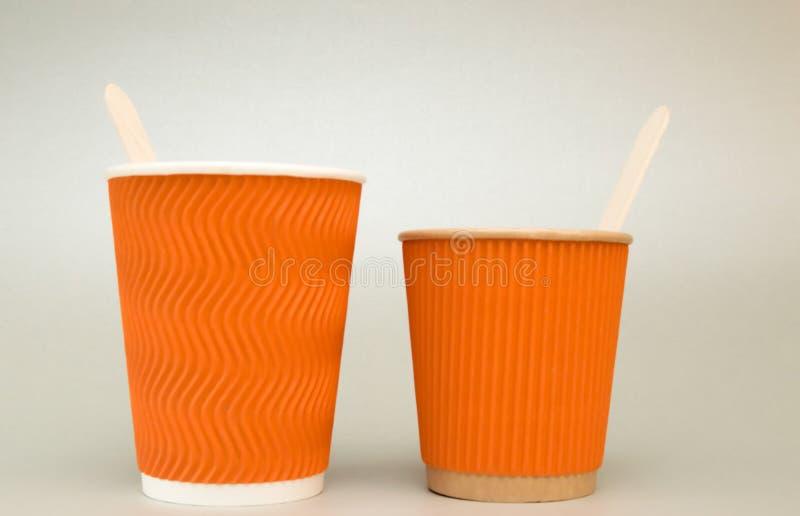 l'arancia due ha scanalato le tazze di carta per il supporto del caff? su un fondo bianco, grande e piccolo con i cucchiai di leg fotografia stock