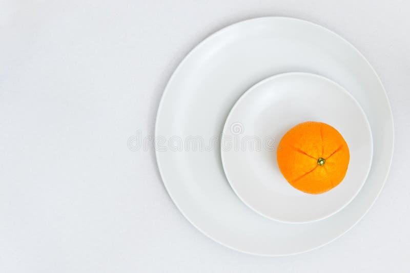 L'arancia fresca su due piatti bianchi con carta ha strutturato il fondo fotografia stock