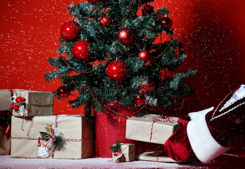 L'arbre de Noël décoré des boules d'ornement de patchwork et des mains rouges du père noël a mis des cadeaux de présents de métie photographie stock libre de droits