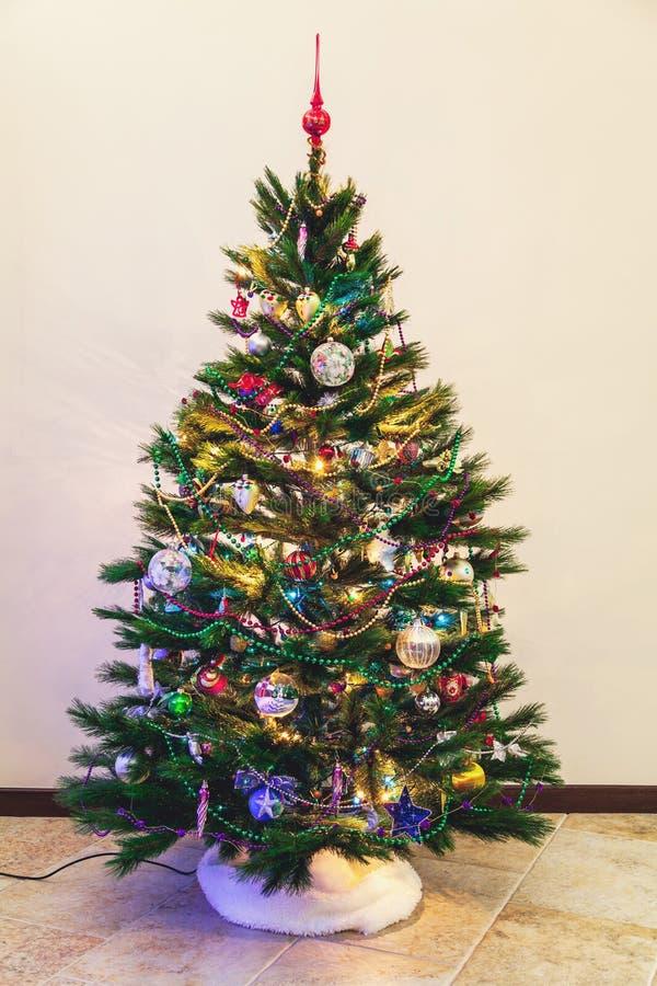 L'arbre de Noël se tient sur le fond blanc de mur image stock