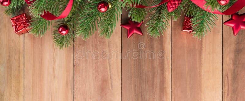 L'arbre de Noël vert part avec les ornements rouges brillants sur le bacground en bois photo libre de droits