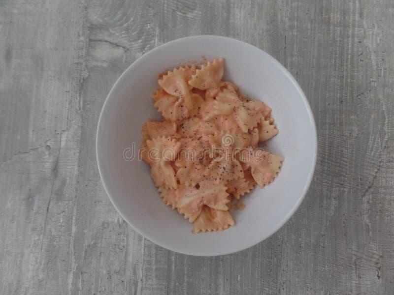 L'arc a formé des pâtes avec de la sauce saumonée image stock
