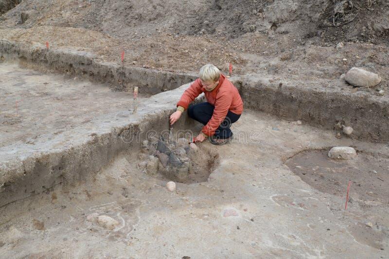 L'archeologo femminile lavora allo scavo con il centro antico fotografie stock