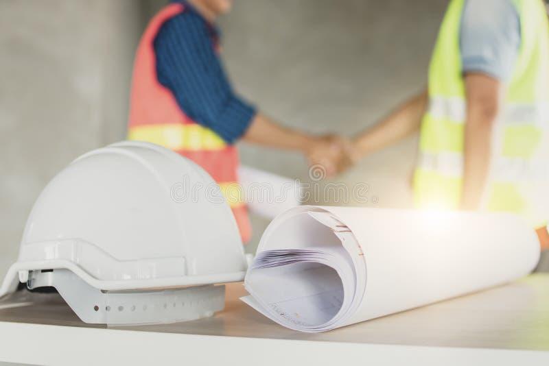 L'architecte font la poignée de main avec le travailleur dans le chantier de construction image stock