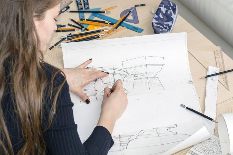 L'architetto della donna disegna un piano, la progettazione, forme geometriche dalla matita sul grande foglio di carta alla scriv immagine stock
