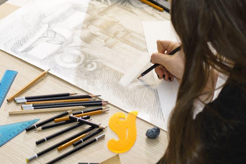 L'architetto della donna disegna un piano, la progettazione, forme geometriche dalla matita sul grande foglio di carta alla scriv immagini stock libere da diritti