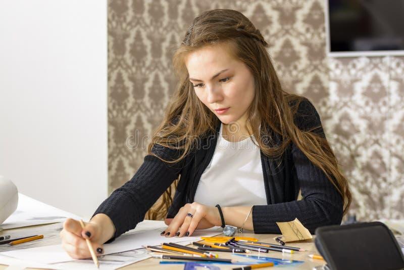 L'architetto della donna disegna un piano, la progettazione, forme geometriche dalla matita sul grande foglio di carta alla scriv fotografie stock