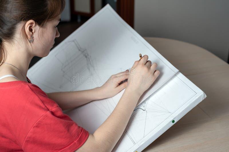 L'architetto dello studente prepara un lavoro del progetto, estrae una matita su una compressa bianca immagine stock libera da diritti