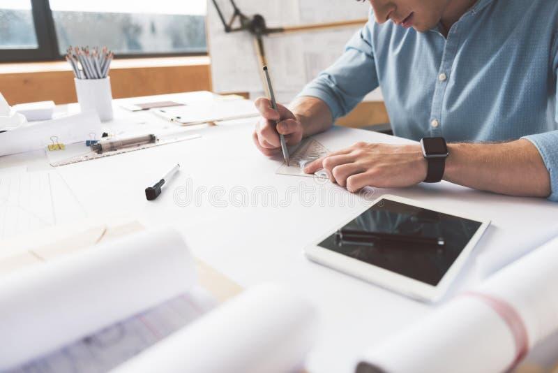 L'architetto giovanile serio sta lavorando in ufficio immagini stock libere da diritti