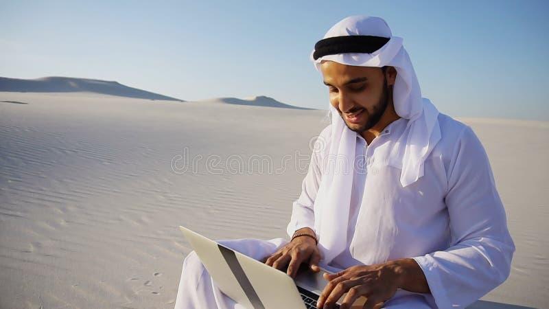 L'architetto musulmano maschio istruito di sceicco dei UAE dell'Arabo si siede con gadg fotografie stock libere da diritti