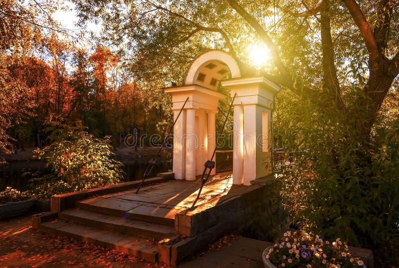 L'arco bianco antico dell'entrata al ponte nel parco della città, in autunno i raggi del ` s del sole fa il loro modo attraverso  fotografia stock