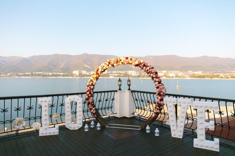 L'arco di nozze decorato con le grandi lettere ama e lampade, posto di cerimonia per la sposa e sposo, la decorazione, fiori rosa fotografia stock