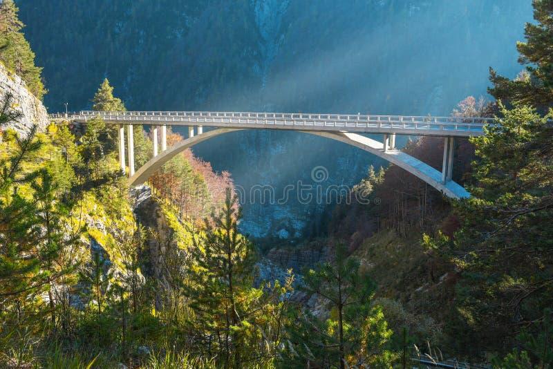 L'arco ha modellato il ponte sopra il fiume vicino ad una strada che capo al livello della sella di Mangart nelle alpi di Julian fotografia stock libera da diritti