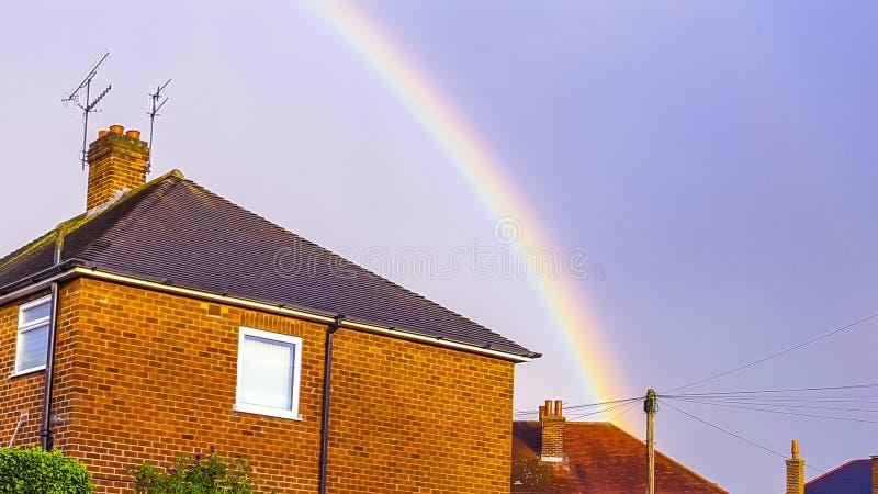 L'arcobaleno fine sopra il tetto rosso ha spleso con il sole fotografia stock libera da diritti