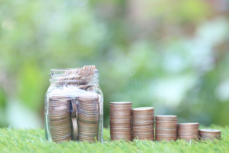 L'argent d'économie pour préparent dans le futur concept, la pile d'argent de pièces de monnaie et la bouteille en verre sur le f images libres de droits
