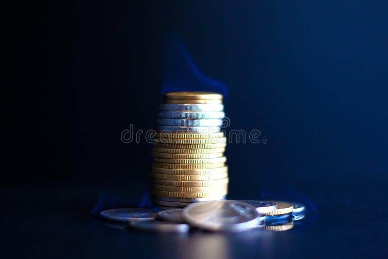 L'argent de concept s'épuise rapidement, des pièces de monnaie en métal brûlent avec une flamme bleue photos stock