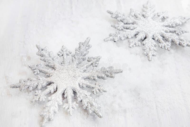 L'argento due ha brillato ornamenti dei fiocchi di neve nella neve fotografia stock