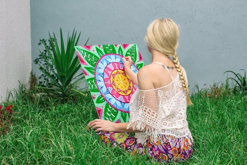 L'aria aperta di verniciatura, una bionda della giovane donna disegna una mandala sulla natura che si siede nell'erba fotografie stock libere da diritti