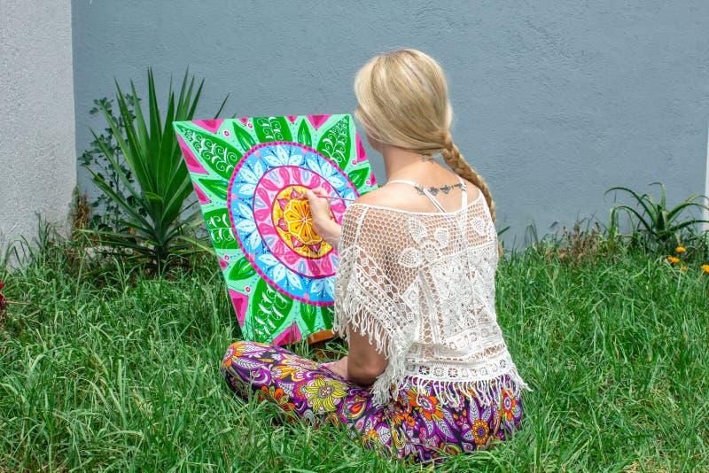 L'aria aperta di verniciatura, una bionda della giovane donna disegna una mandala sulla natura che si siede nell'erba fotografia stock libera da diritti