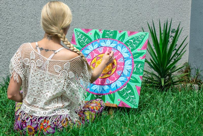 L'aria aperta di verniciatura, una bionda della giovane donna disegna una mandala sulla natura che si siede nell'erba immagini stock libere da diritti