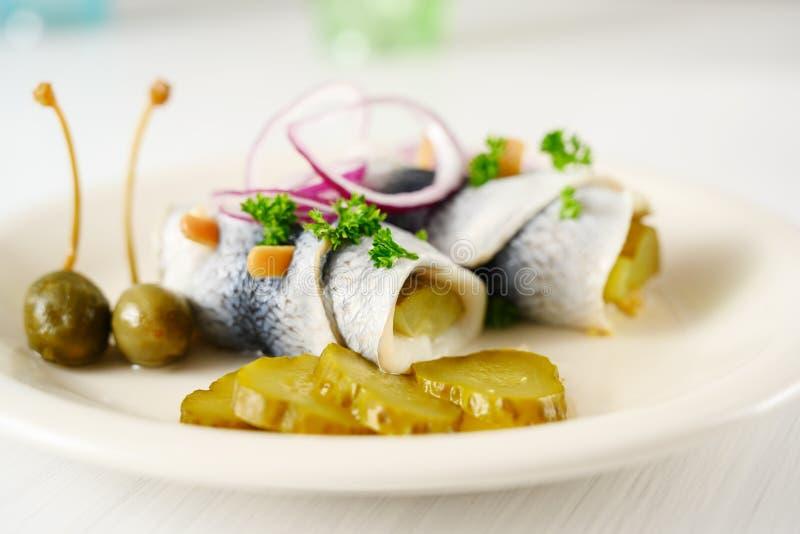 L'aringa marinata rotolata, inoltre ha chiamato i rollmops con le cipolle rosse, cetriolini ed i capperi come pasto di postumi di fotografie stock