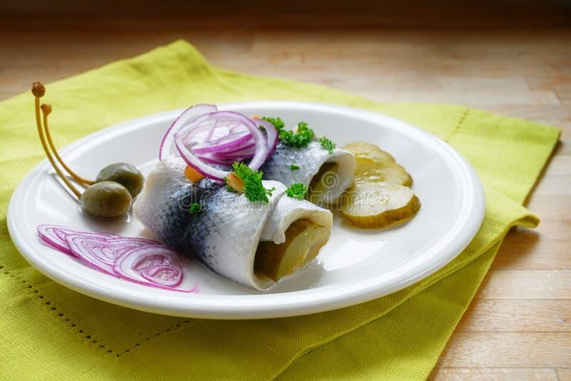 L'aringa marinata rotolata, inoltre ha chiamato i rollmops con le cipolle rosse, i cetriolini ed i capperi come prima colazione t fotografie stock libere da diritti