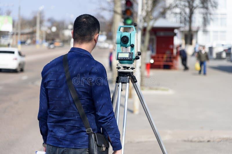 L'arpenteur de terre d'ingénieur fait des mesures sur la rue de la ville de Tchernigov, Ukraine photographie stock