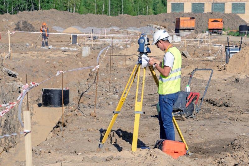 L'arpenteur exécute l'enquête topographique du secteur pour le DAO photographie stock libre de droits