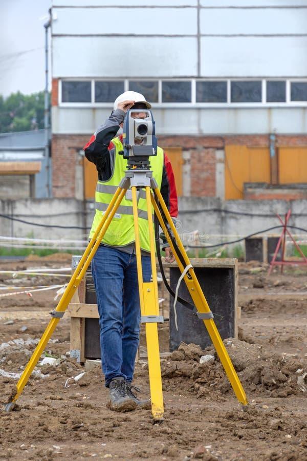 L'arpenteur fait des mesures pour le cadastre photographie stock libre de droits