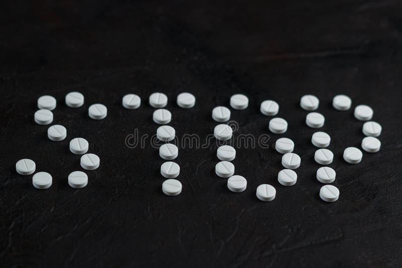 L'arrêt d'inscription a présenté des pilules sur un fond foncé de béton photo libre de droits