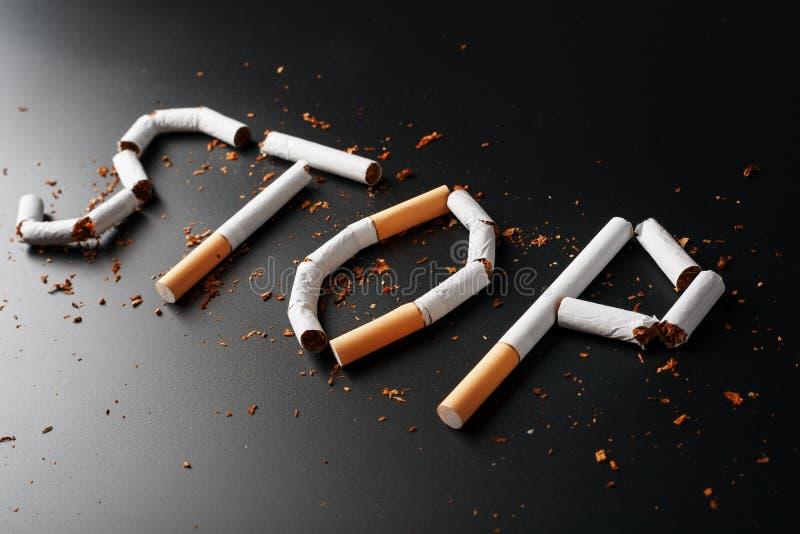 L'ARR?T d'inscription des cigarettes sur un fond noir Cessez le fumage Le concept des mises ? mort de tabagisme Inscription de mo photos stock